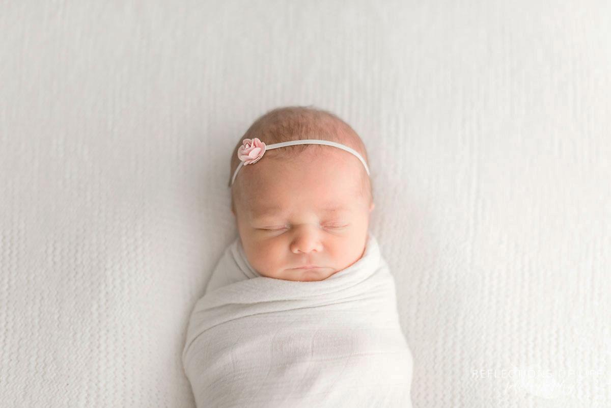 Little newborn bby girl swaddled in little white unicorn blanket with small rose headband
