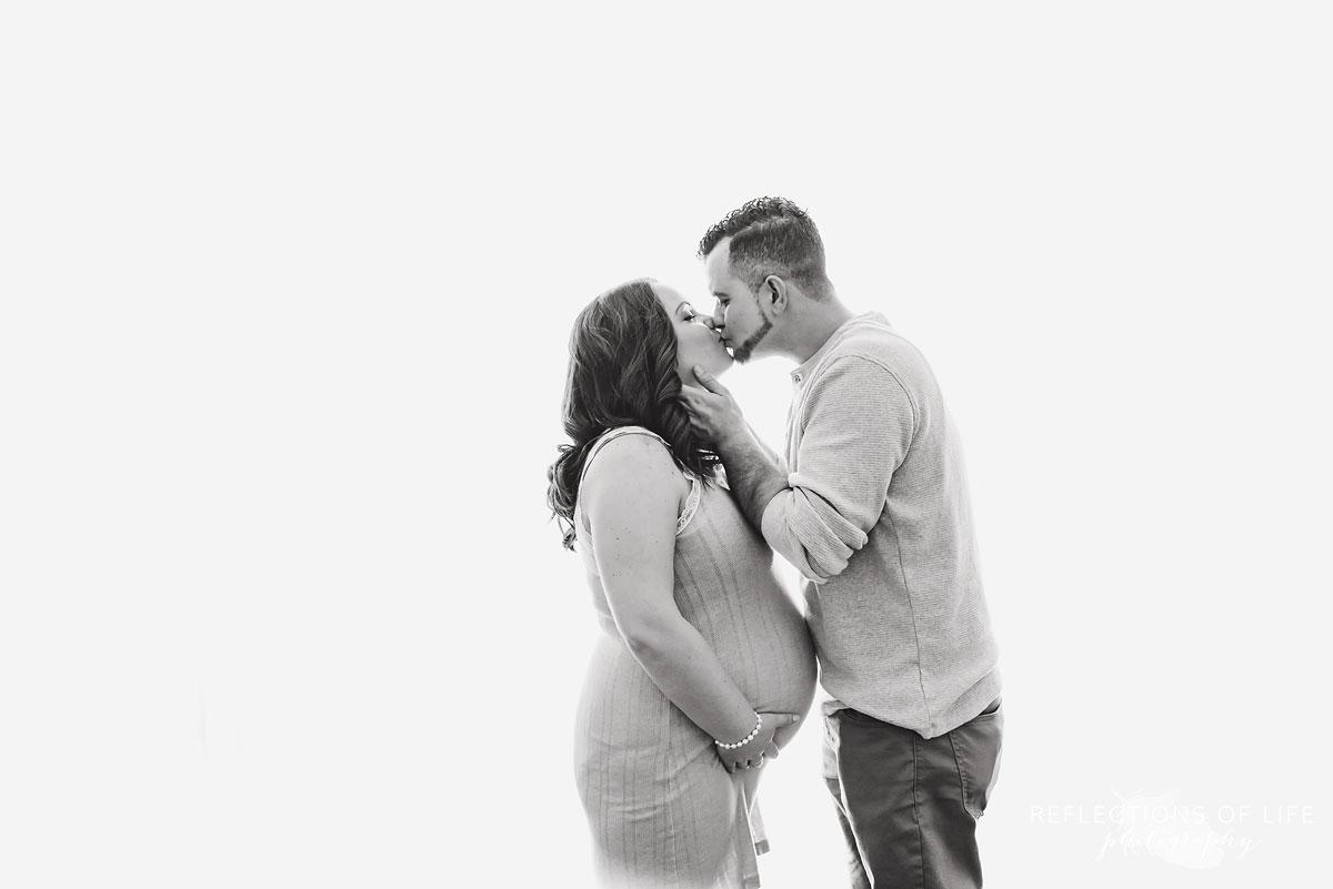 Dad and pregnant mom kissing in natural light studio Niagara Ontario