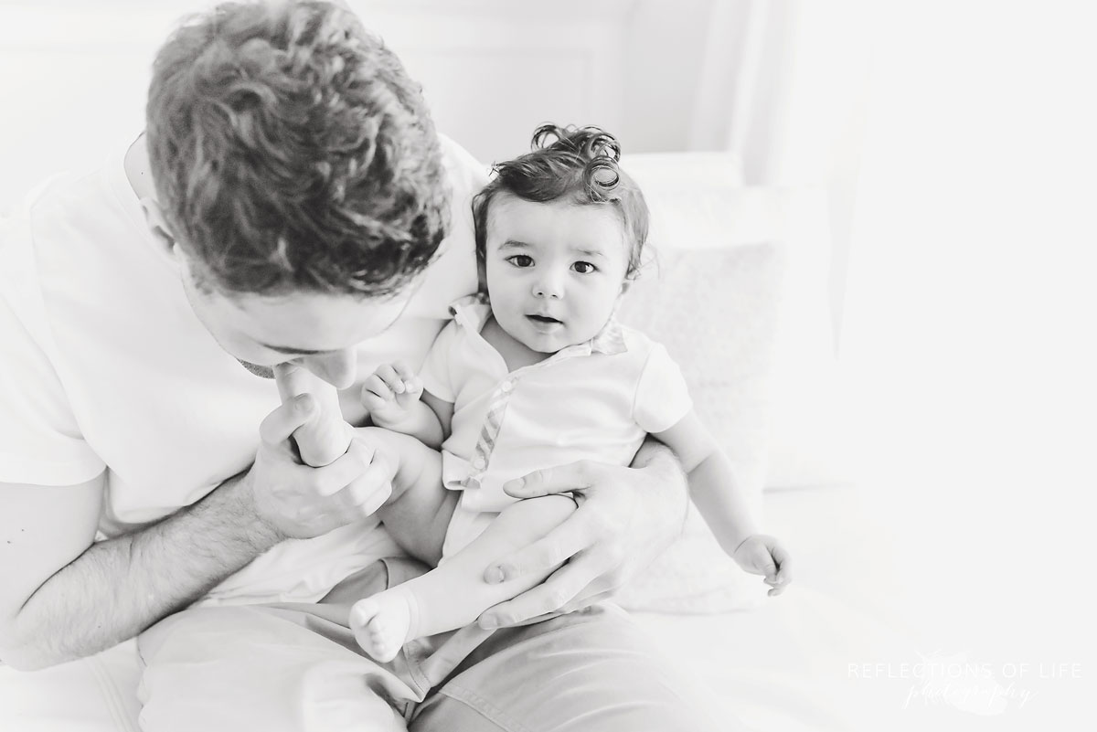 daddy kissing baby's toes in black and white