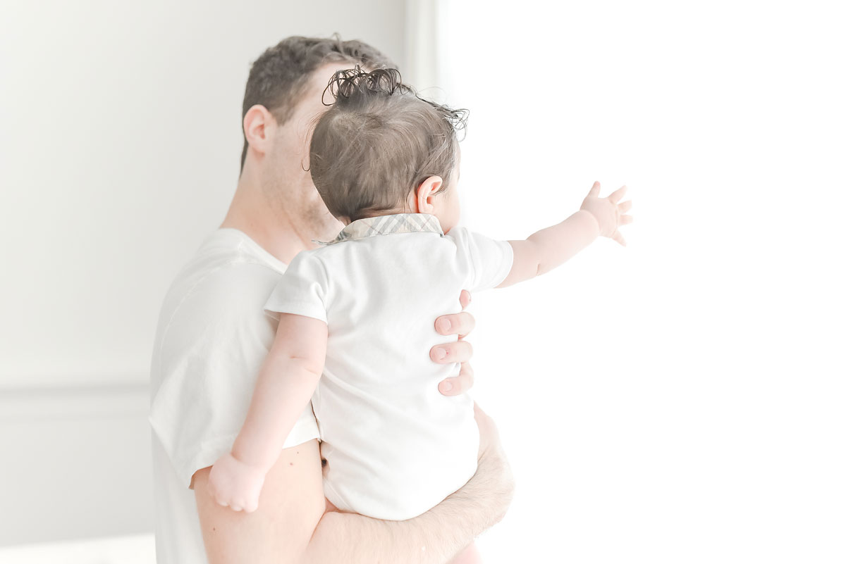 daddy showing baby white curtains in professional photo studio niagara ontario