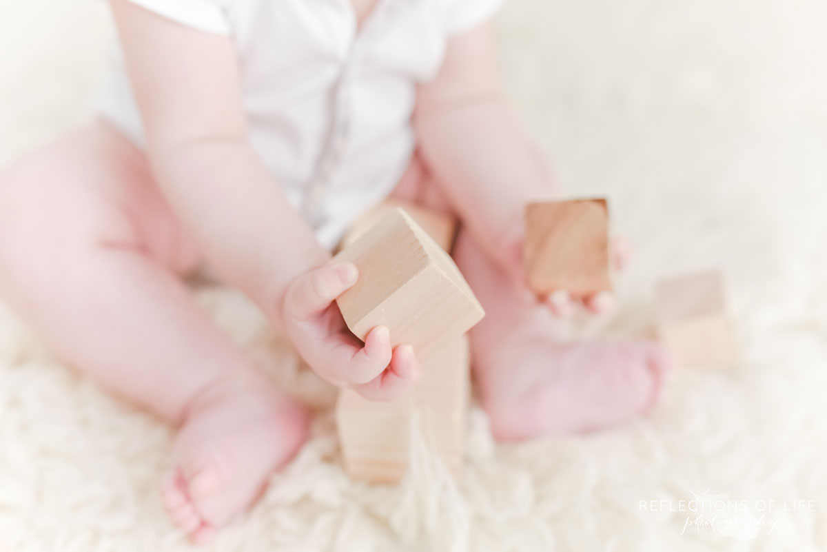 baby boy playing with wood blocks in photo studio
