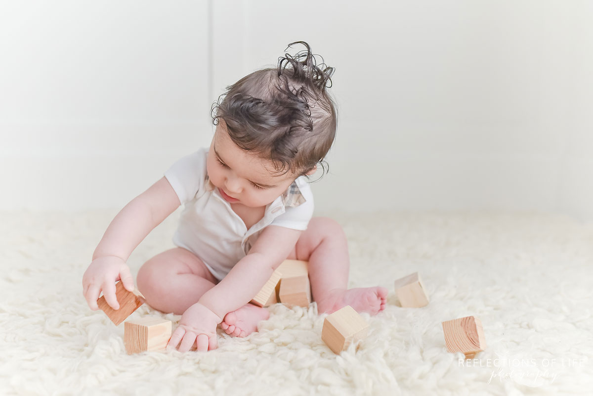 baby boy playing with wood blocks in white studio