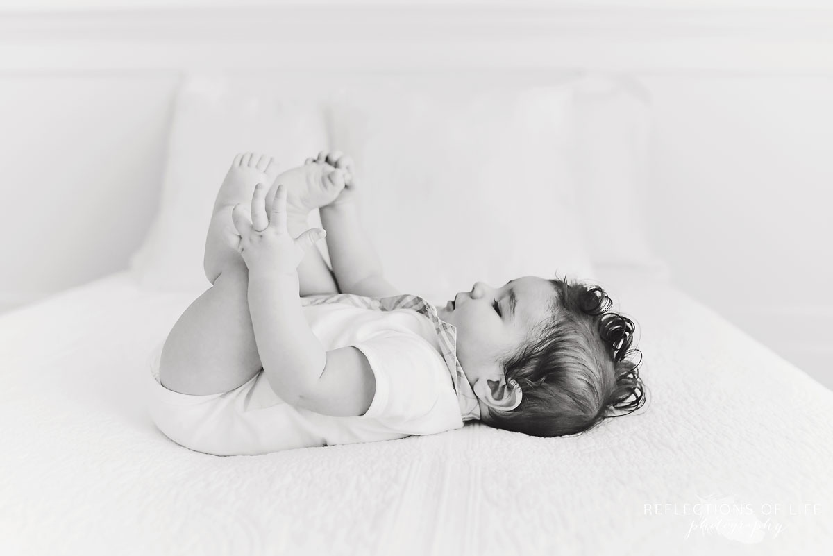 baby boy playing with his toes in black and white