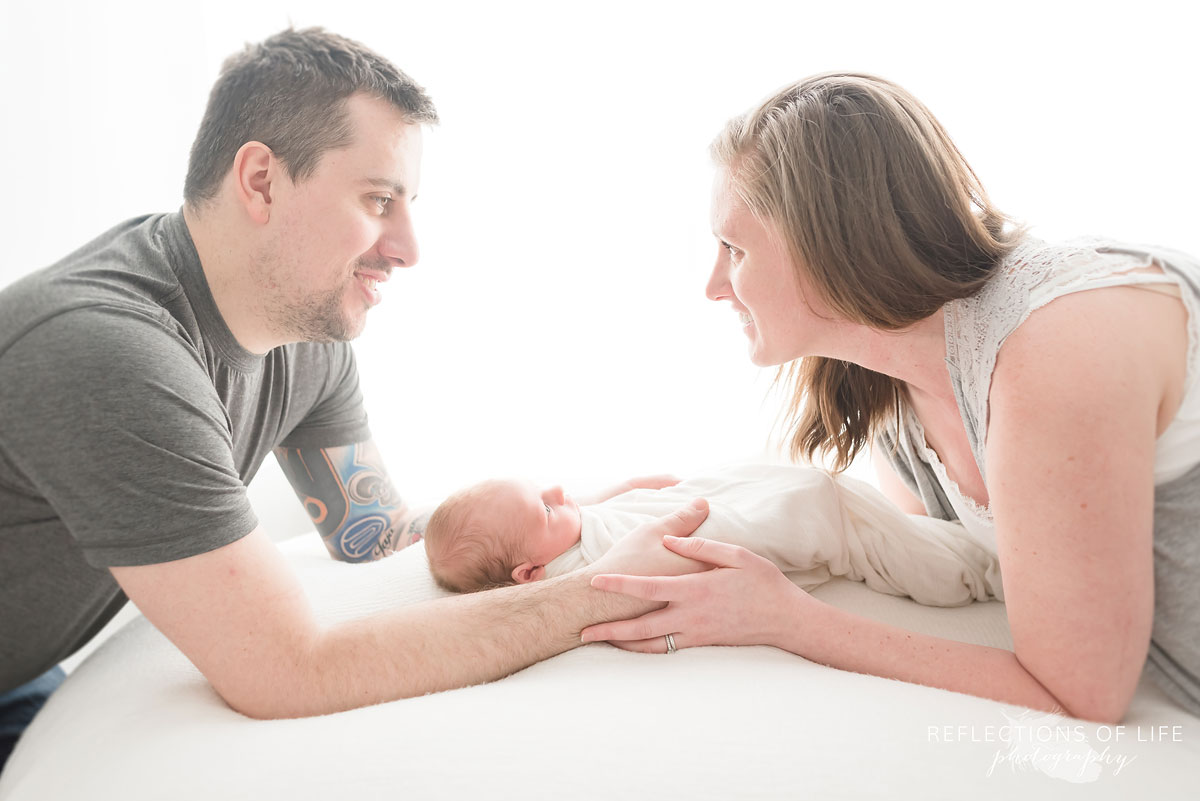 mom and dad with their hands on newborn baby boy