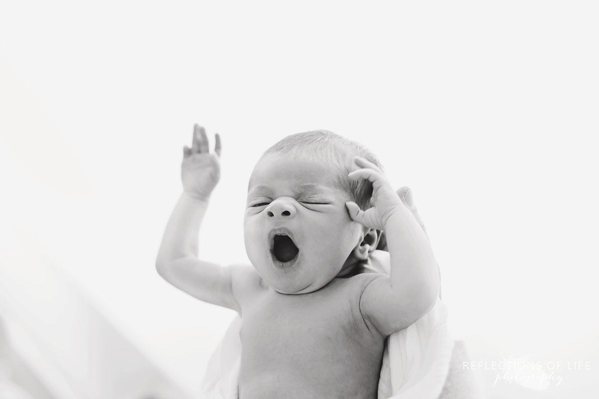 Newborn baby girl yawn in black and white