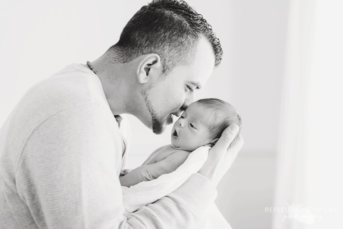 Black and white photo of newborn baby girl and her daddy whispering secrets to her