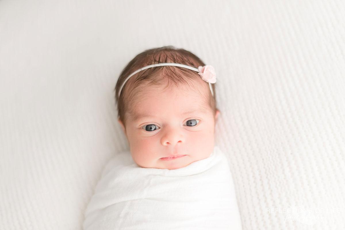 Newborn baby girl looking straight into the camera