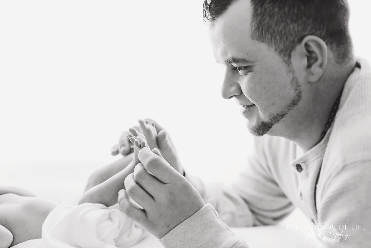 New daddy plays with newborn baby girl toes