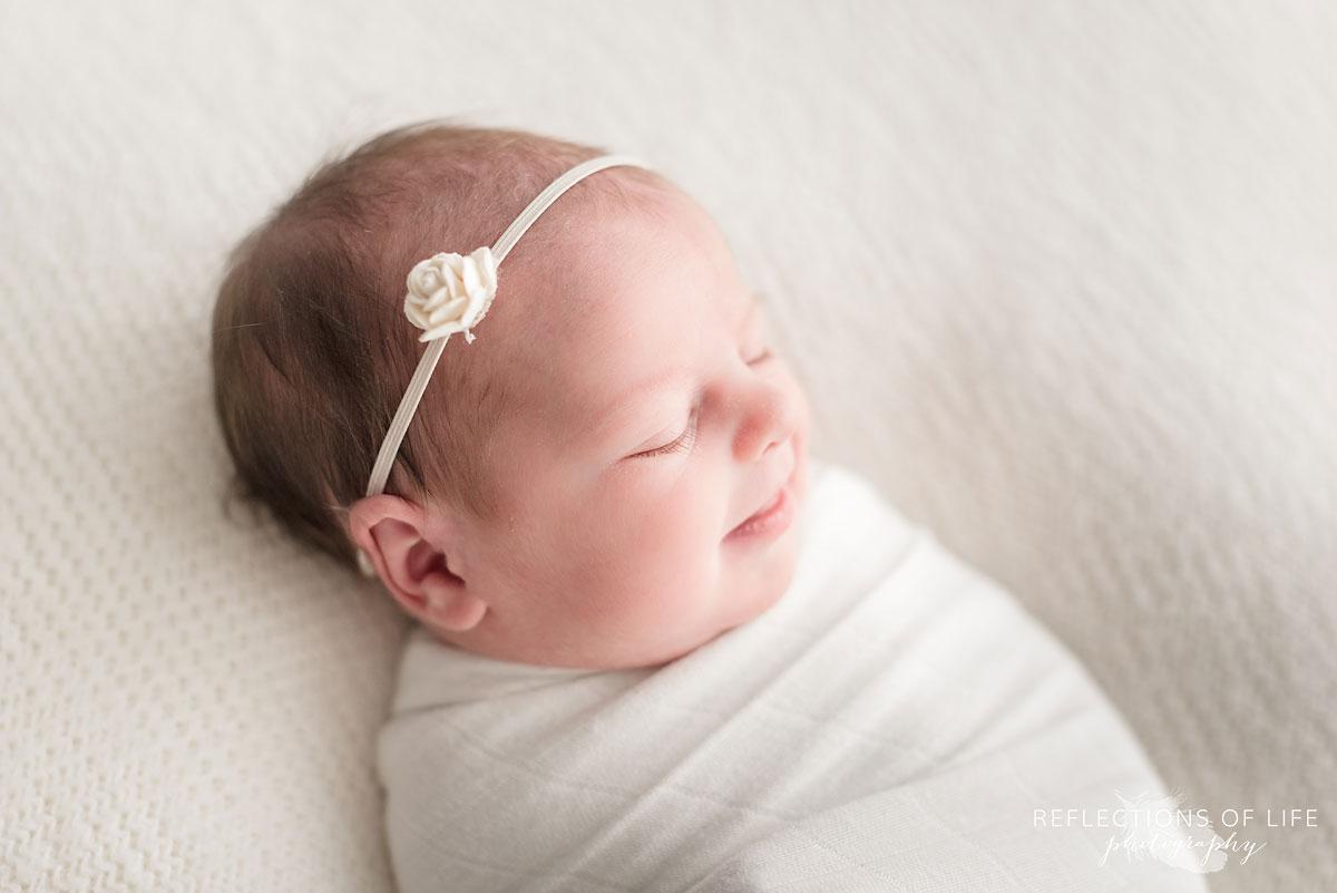 Newborn baby girl with simple white rose headband on beanbag