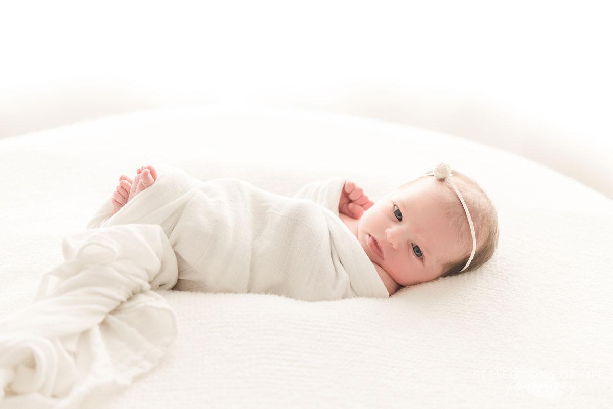 little newborn baby girl wrapped in white on white beanbag