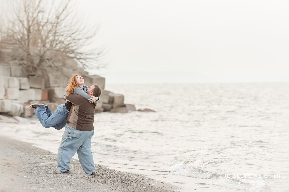 Father lifting daughter up by the beach in Grimsby Ontario