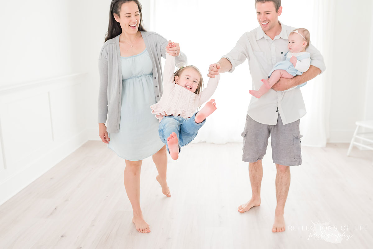 7 Ways To Speak Life, Father and mother swinging daughter in white studio.jpg