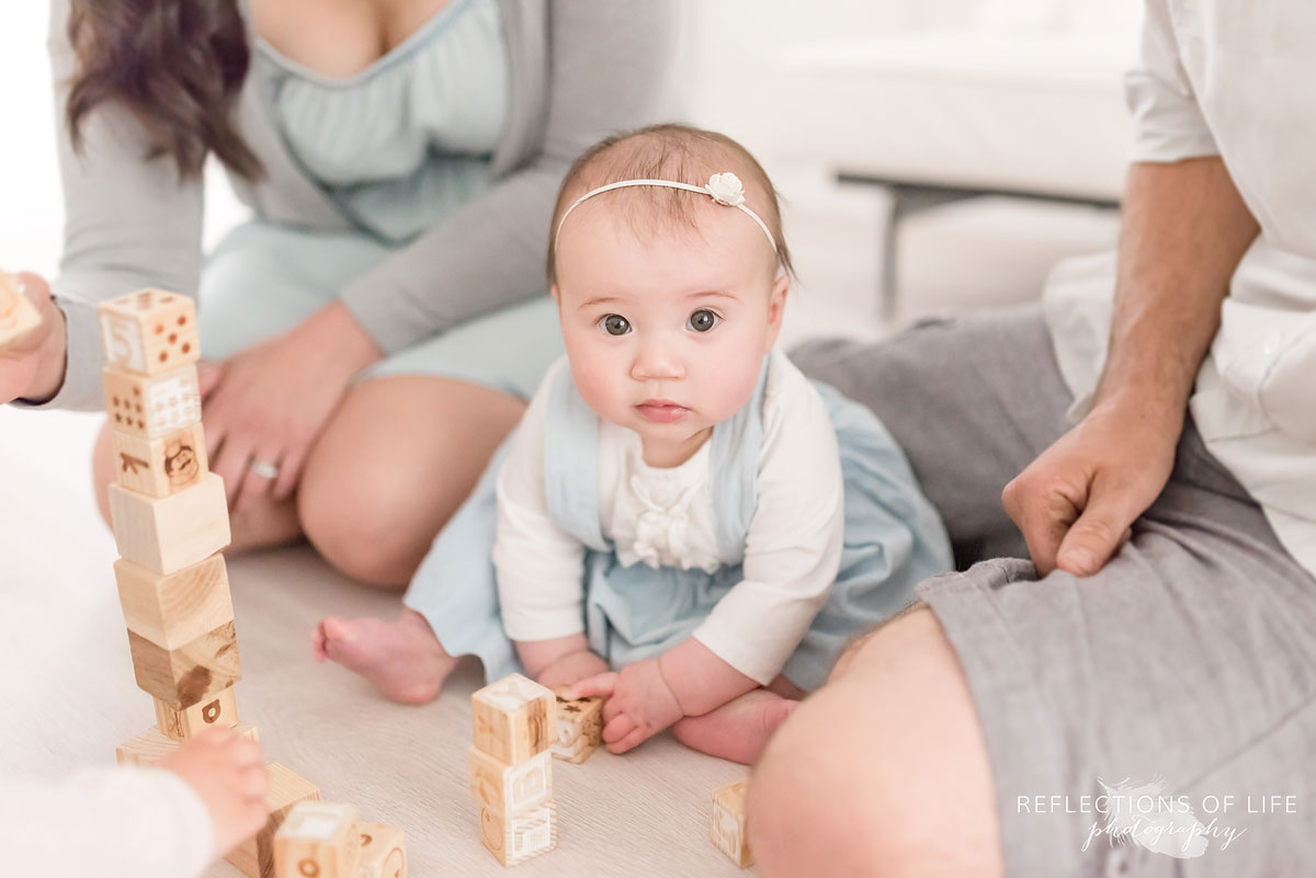 Mother father and baby playing with blocks in studio