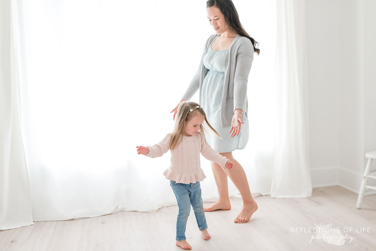 Mother and daughter dancing in white studio
