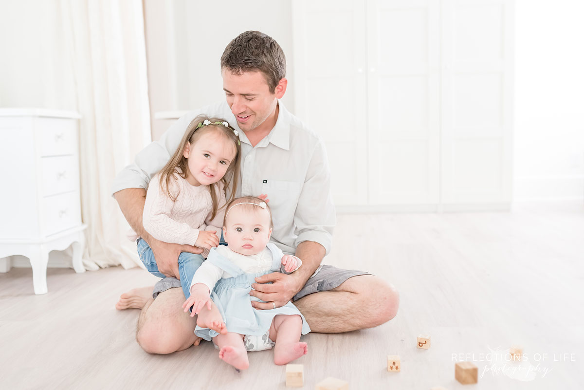 Father and children sitting on floor in white studio