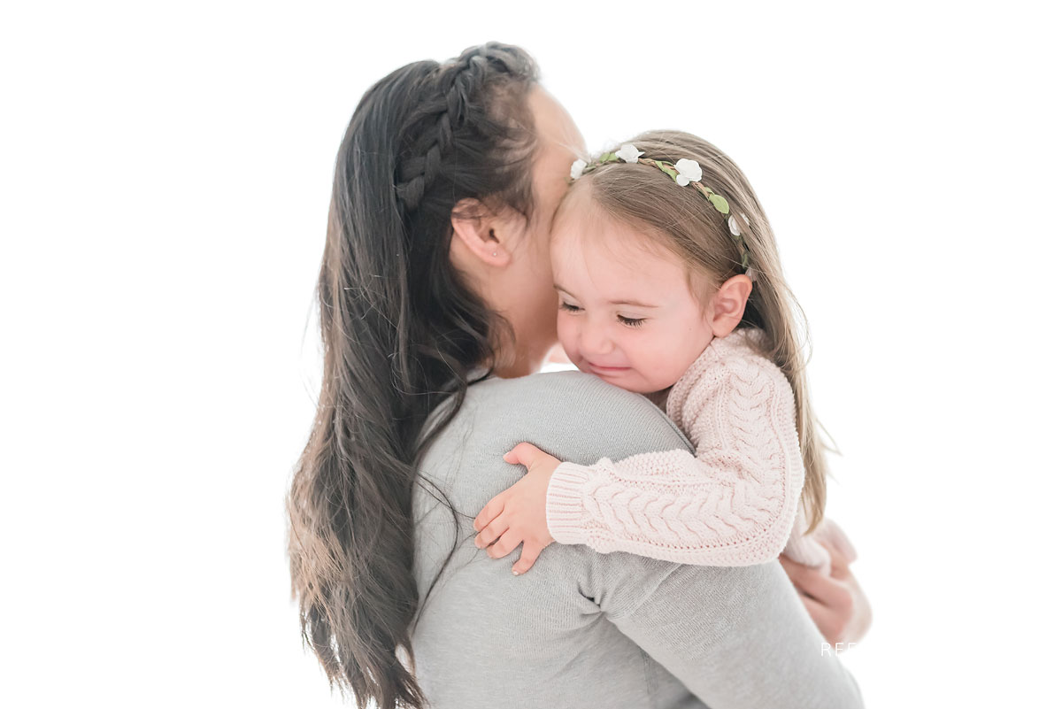 Mother and daughter hugging in white studio