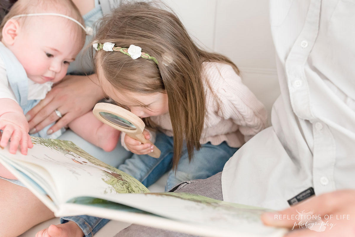 Young girl looking closely at a book on white couch