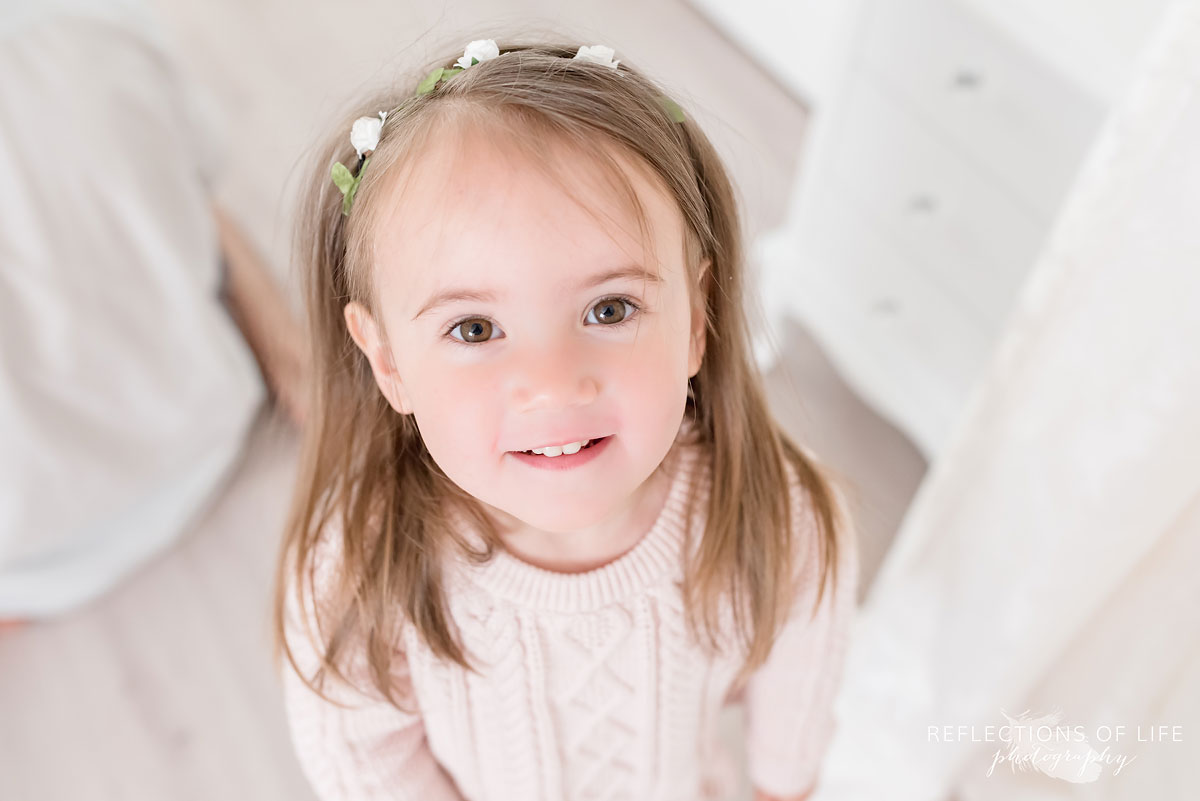 Young girl smiling at camera in white studio