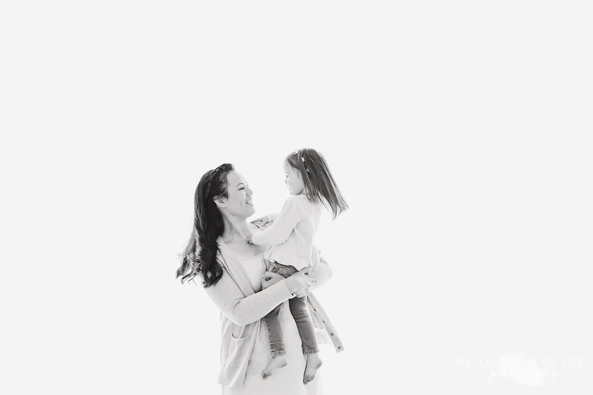 Mother and daughter looking into eachother's eyes in a white studio