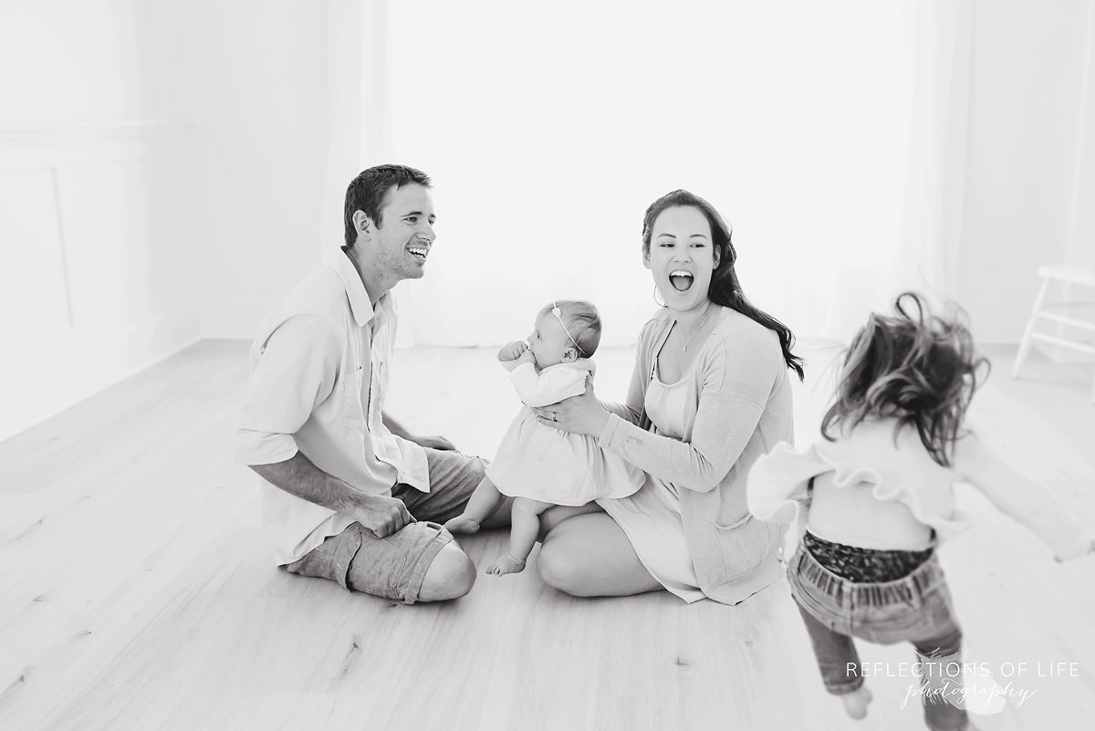 Black and white of family laughing in white studio