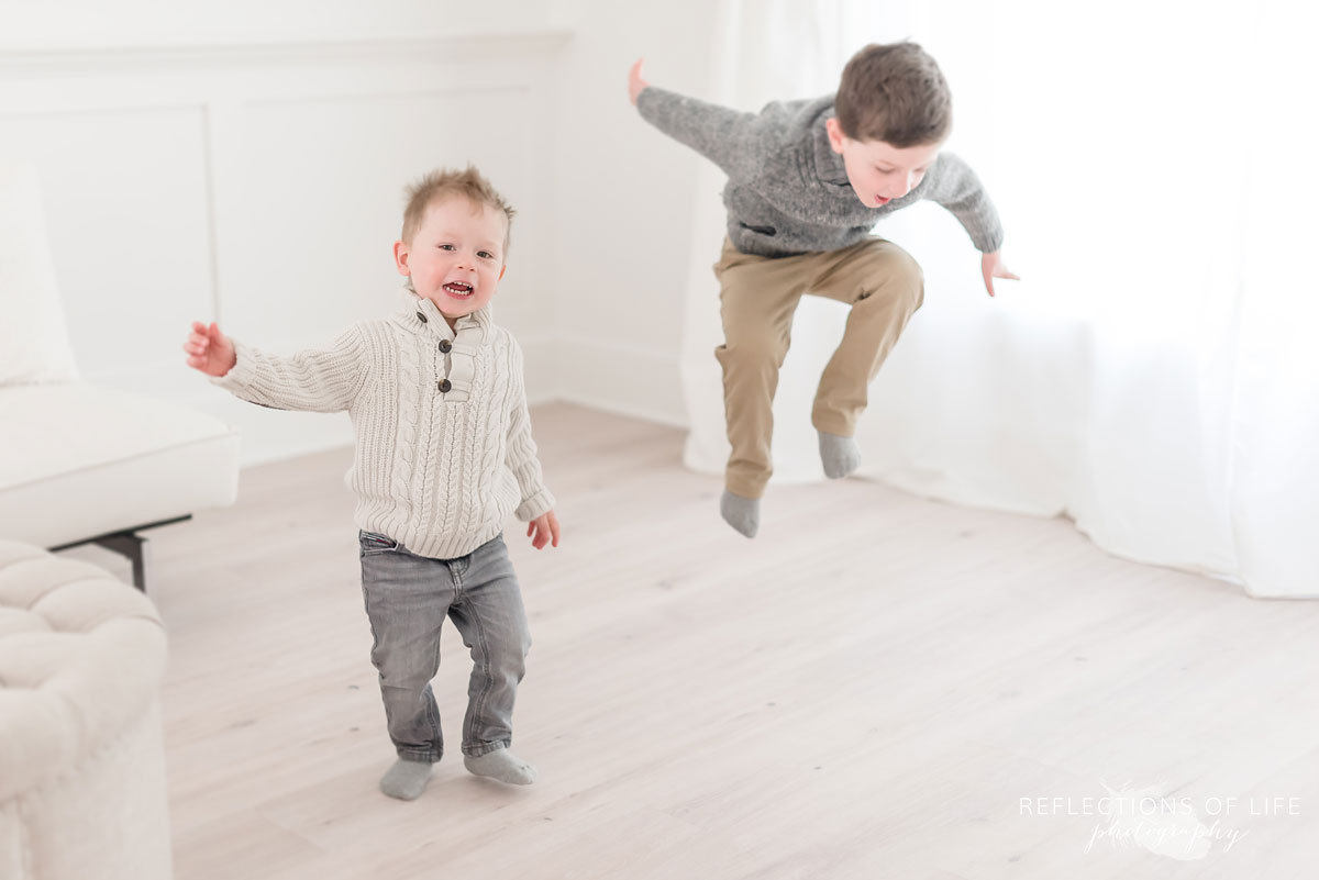 Brothers jumping in natural light studio