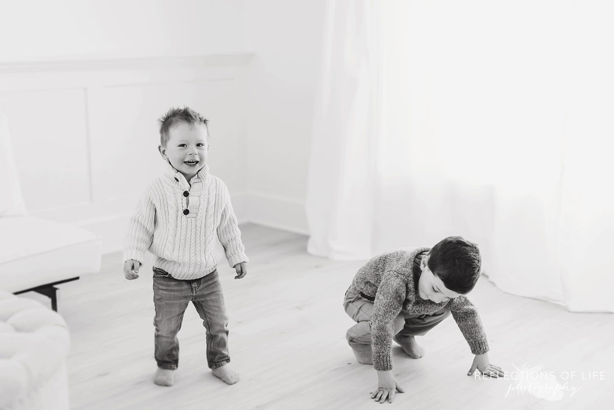 Brothers playing in natural light studio black and white