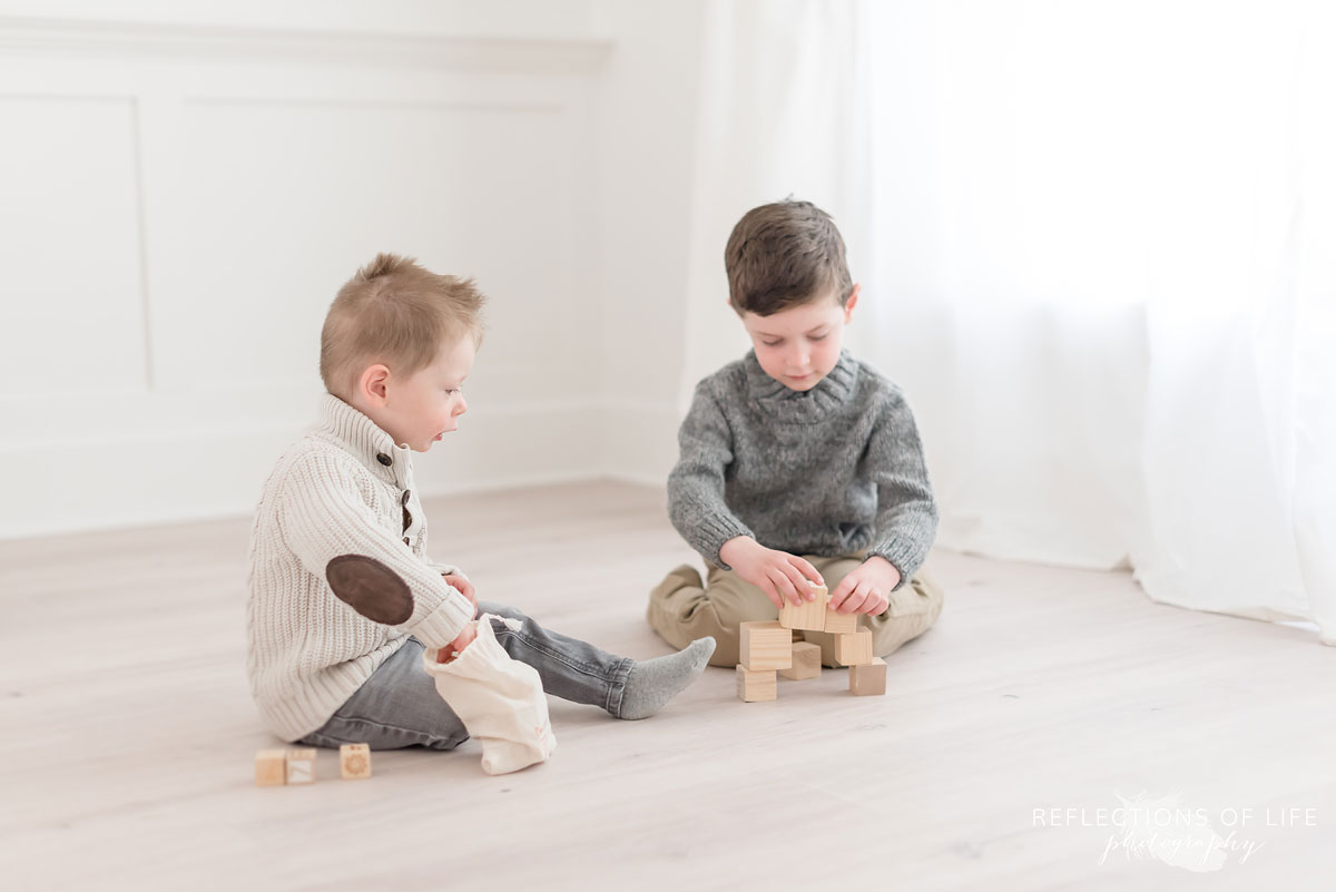 Brothers building block towers in natural light photo studio