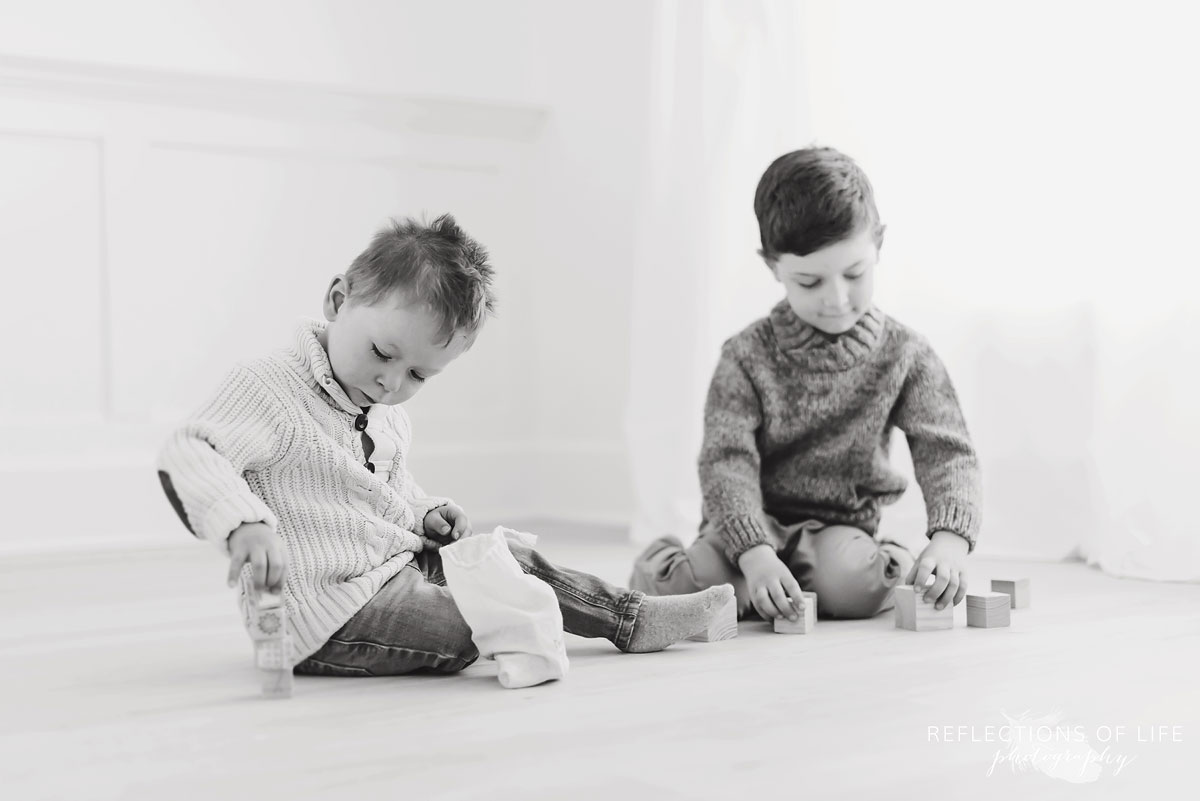 Brothers building wooden block towers in black and white
