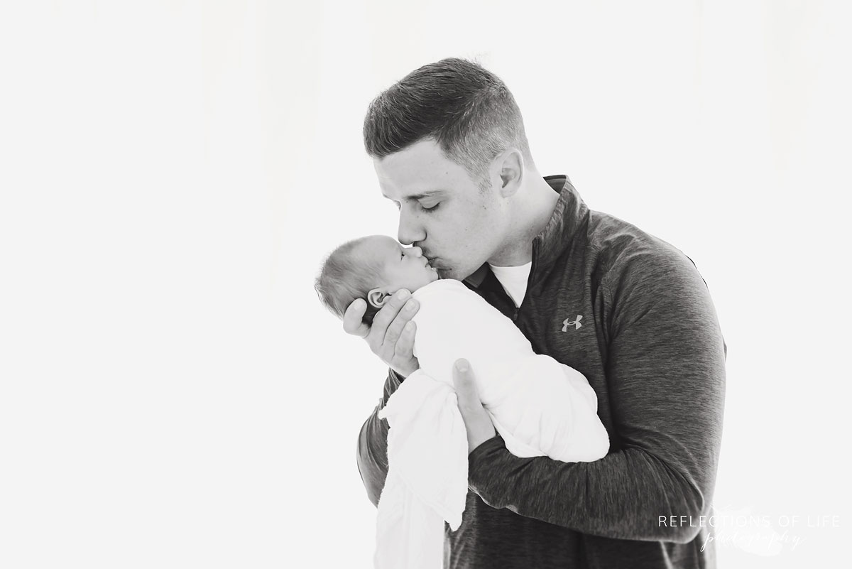 Father kissing his baby girl black and white