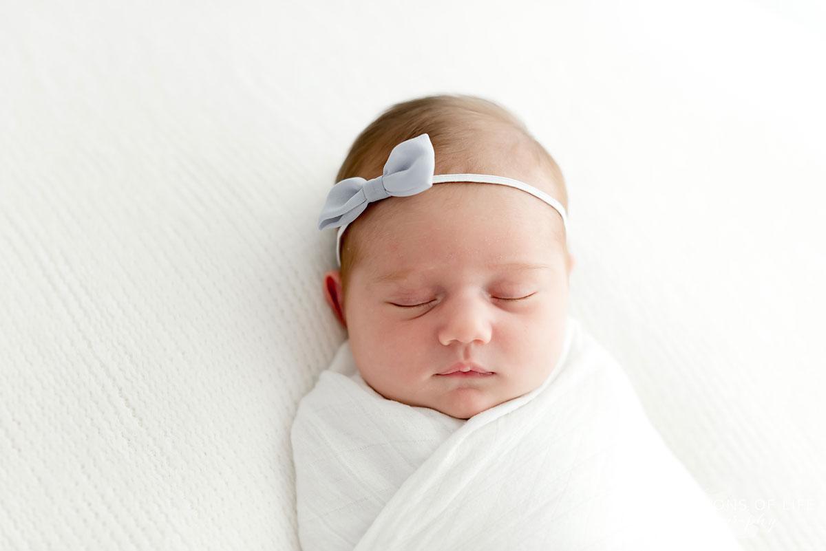 Baby girl with bow headband sleeping