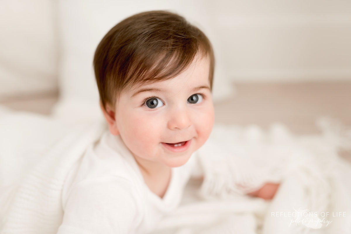 Baby smiling at camera in white studio Grimsby Ontario