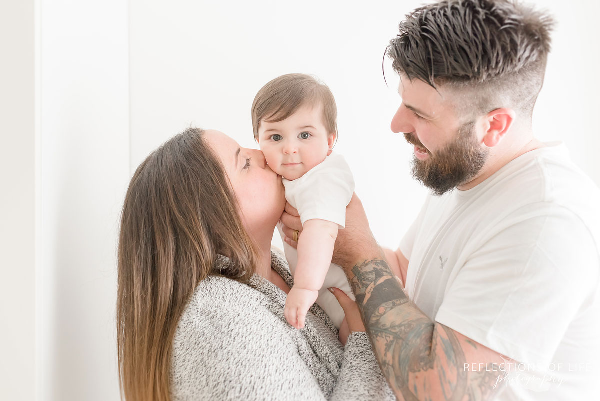 Mom kissing baby and dad holding baby up