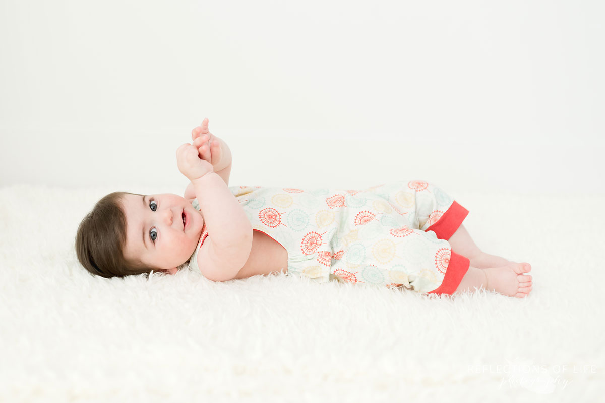 Baby looking at camera on white blanket in white studio
