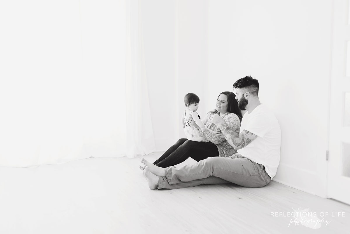 Black and white on mom dad and baby playing on floor