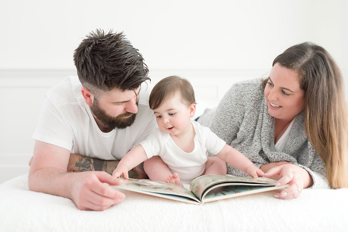Baby closing book with mom and dad