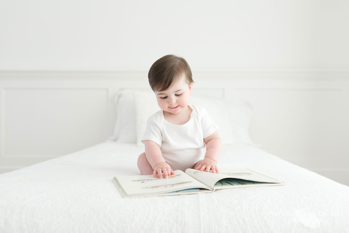 Baby looking at book pages on white couch Niagara Photography