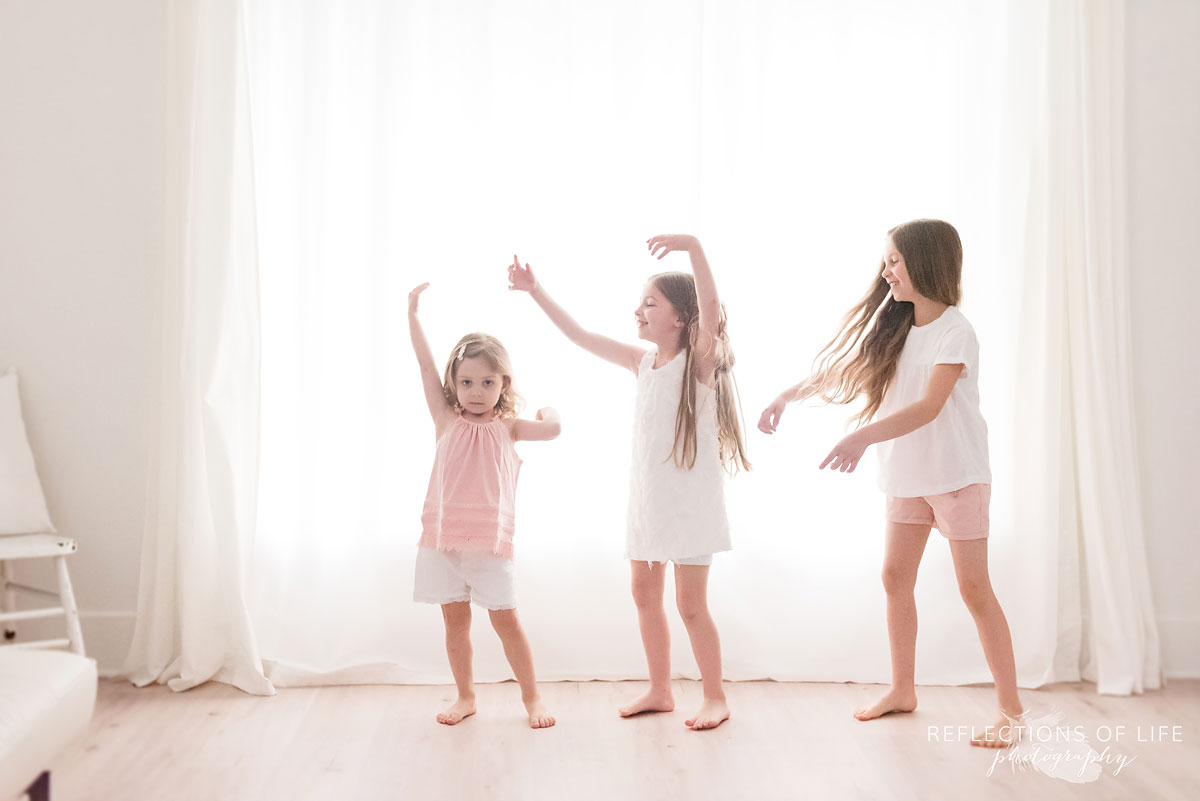 sisters playing together in front of white background
