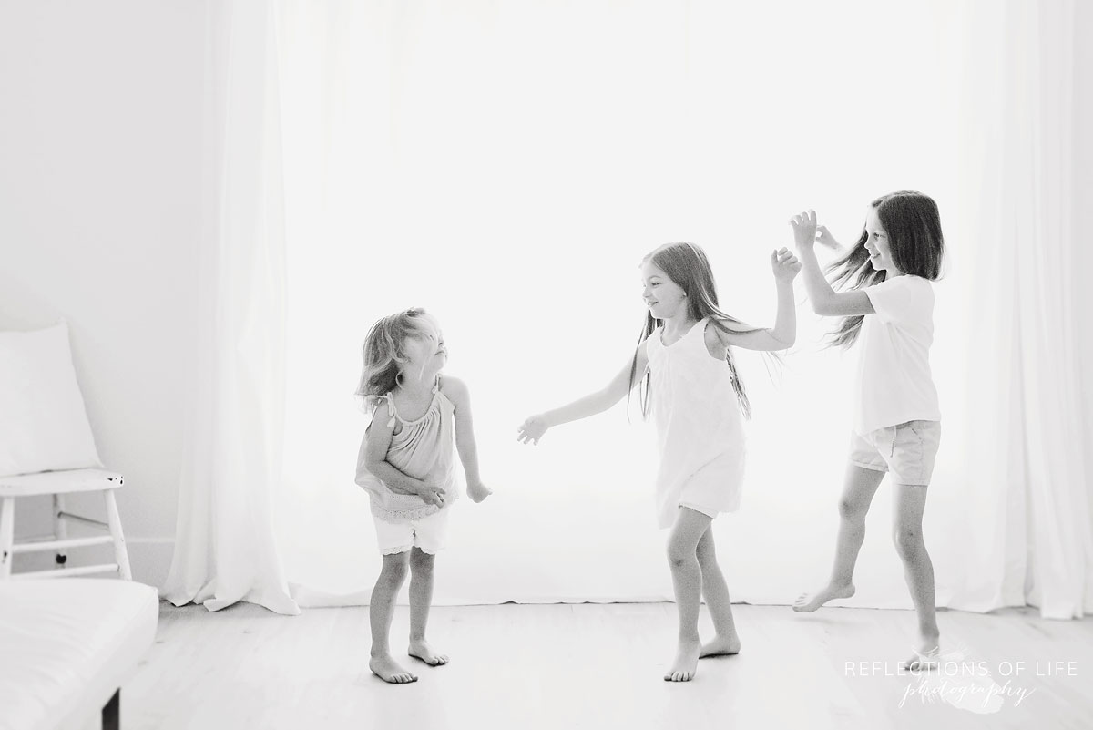 three sisters dancing in white studio