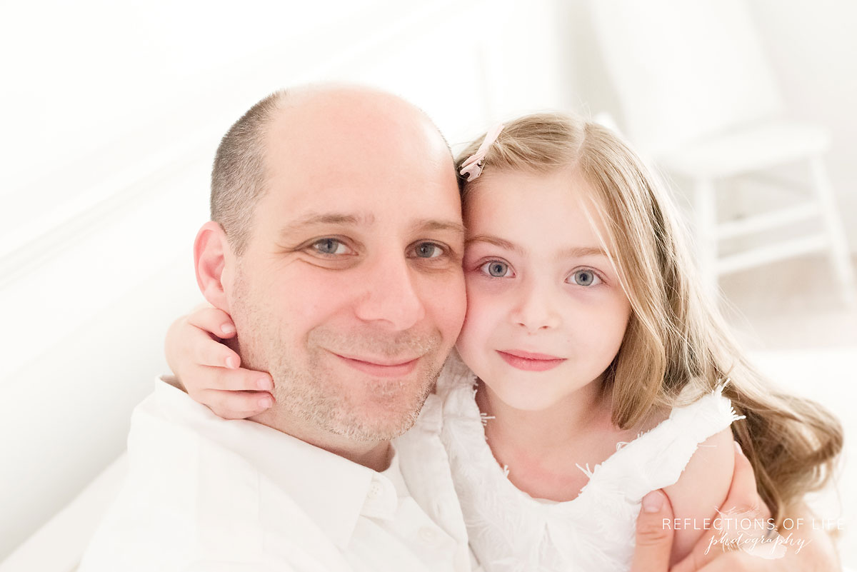 dad and daugther looking into camera smiling