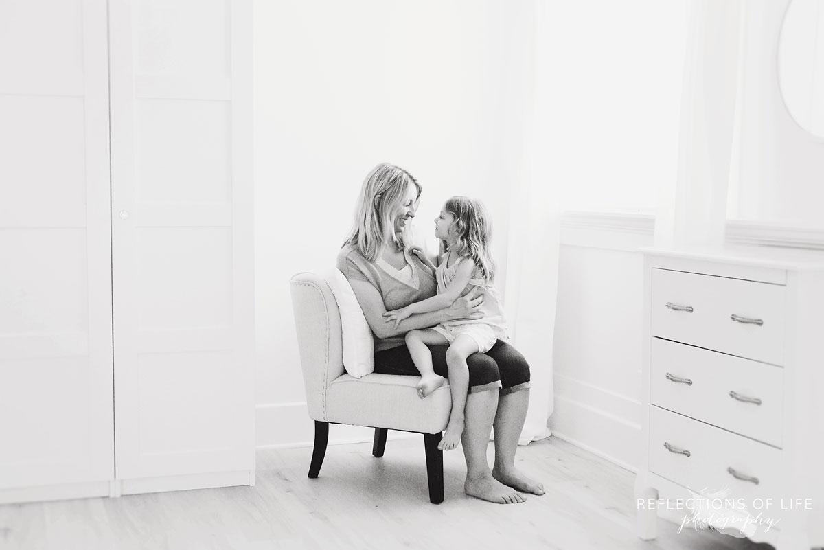 daughter sitting on mom's lap in studio
