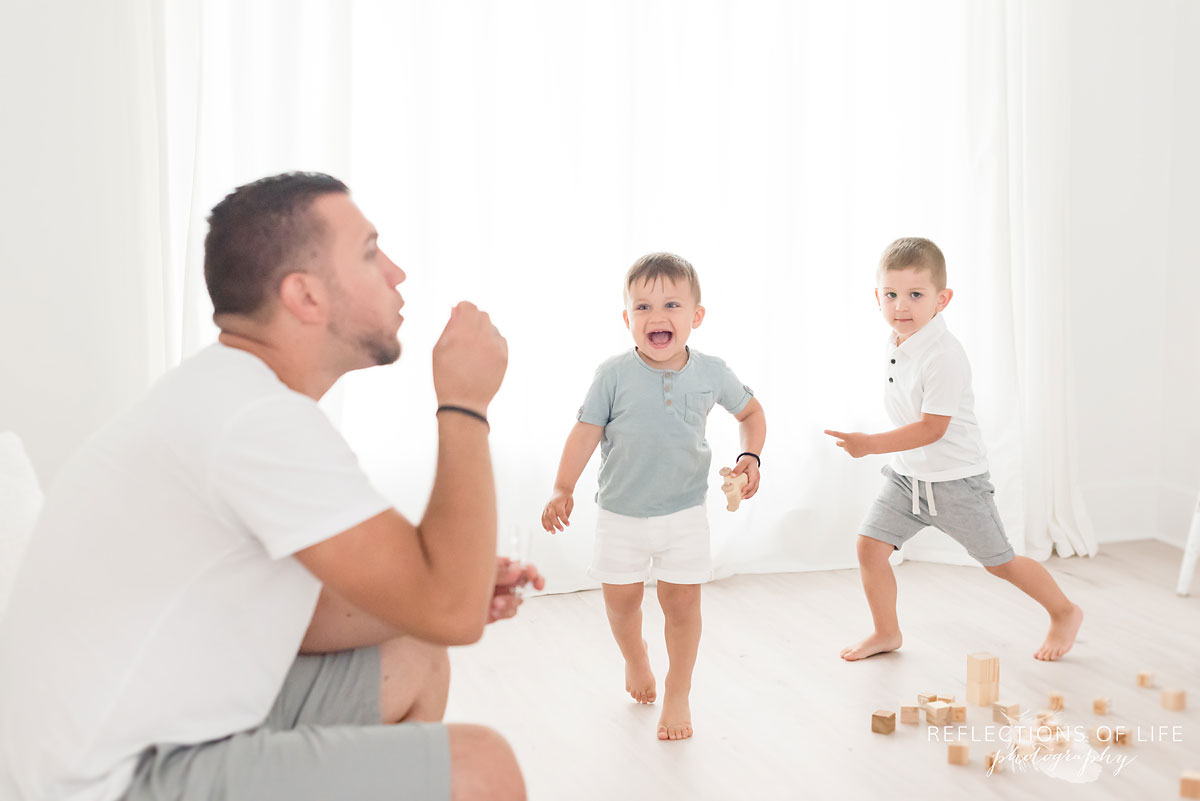 dad and sons blowing bubbles in studio