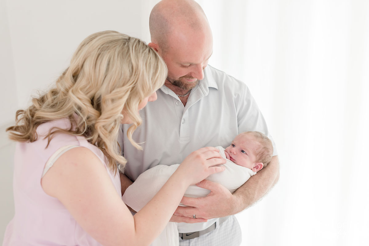 mother and father with baby in white background studio