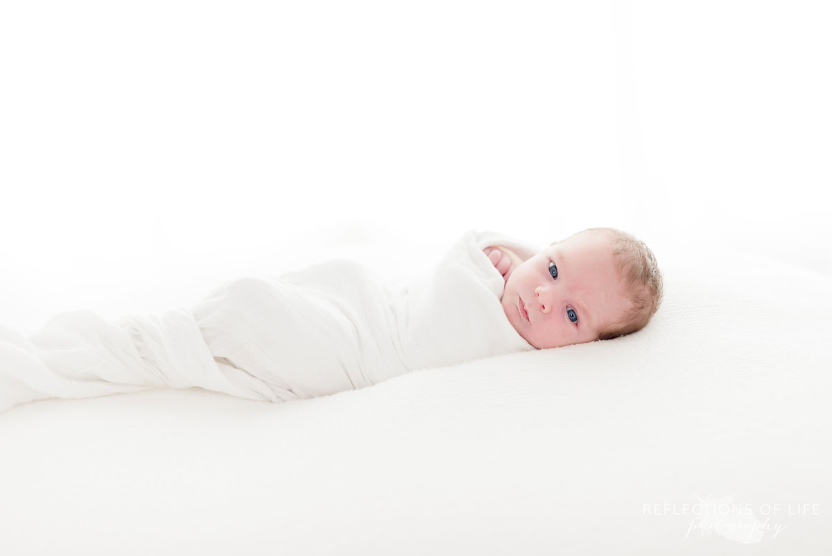 newborn baby on pillow wrapped in blanket