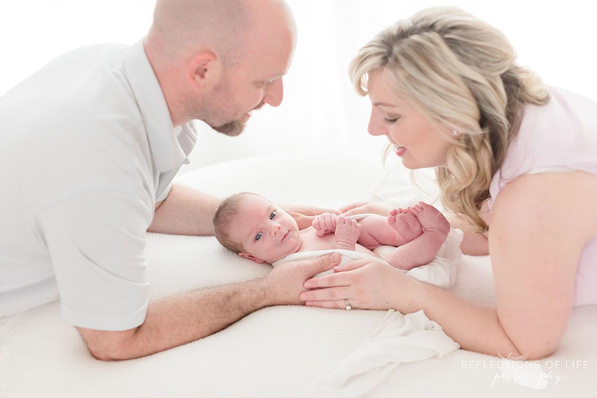 mom and dad holding baby on pillow in studio