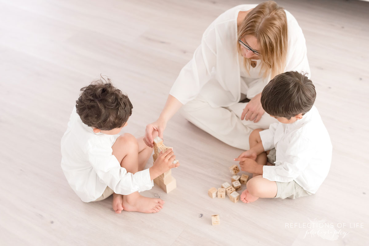 mother and sons playing with blocks together on floor of studio