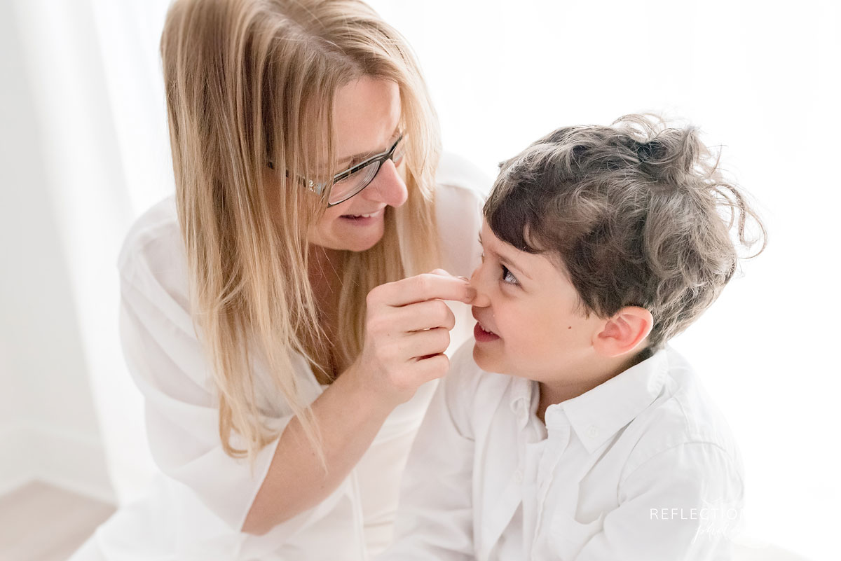 portrait of mom touching son's nose