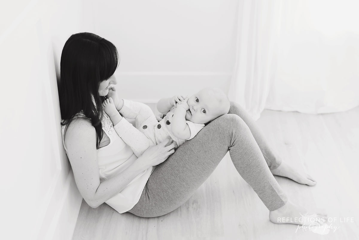 mom and baby sitting together in studio black and white.jpg