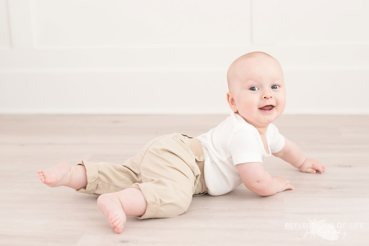 baby laying on stomach on floor looking at camera.jpg