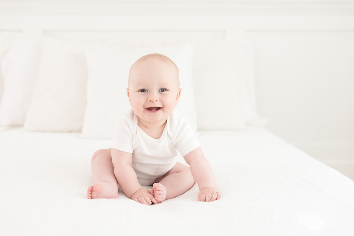 baby sitting on white bed in studio.jpg