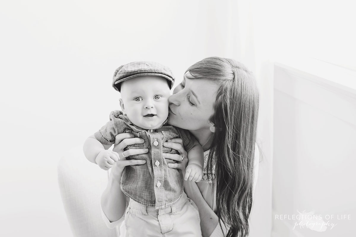 mother giving baby a kiss on the cheek in studio black and white.jpg